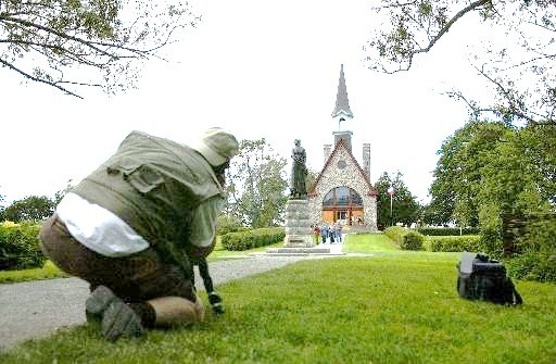 A visitor photographs the iconic statue of Evangeline, heroine of Longfellow's epic poem about the Acadian expulsion, at the deportation memorial in Grand-Pré, Nova Scotia. (Times-Picayune photo by Brett Duke)